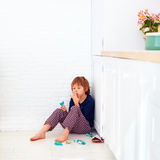 Sweet tooth kid hiding in kitchen corner, eating candies Stock Photos