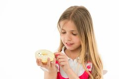 Sweet treasure. Girl calm face carefully holds sweet donut in hand, isolated white. Kid girl with long hair likes donuts. Snack concept. Child likes to eat Stock Photography