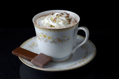 Sweet Treat. A cup of hot chocolate rests on a china saucer. The hot chocolate has whipped cream on top. Two pieces of chocolate rest on the saucer. The  cup Royalty Free Stock Image