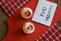 Cupcakes and loving sentiment on a wood background. Sweet treats on a red board and checkered towel Royalty Free Stock Photo