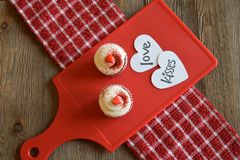 Cupcakes and loving sentiment on a wood background. Sweet treats on a red board and checkered towel Stock Photo