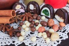 Sweet treats on a table. Sweet treats on a lace doily. Candies, hazelnut, walnut, cinnamon Stock Image