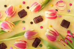 Sweet tulips. Sweets and tulips arranged on yellow background; upview Royalty Free Stock Image