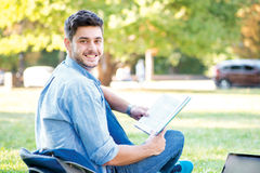 Sweet university life. Cute male student holding a laptop and re. Ading a book and looking away while sitting on the grass near the campus of the University at Royalty Free Stock Photos