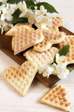 Sweet wafer hearts on dish with flowers Stock Photos