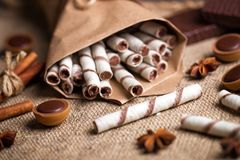 Sweet wafers rolls,  caramel candies and chocolate on a burlap Royalty Free Stock Image