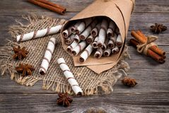 Sweet wafers rolls,  caramel candies and chocolate on a burlap Stock Photography