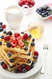 Waffle with berries. Sweet waffle with berries, milk and honey on white wooden table Royalty Free Stock Photography