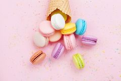 Sweet waffle cone with macaron or macaroon on pink pastel background top view. Flat lay composition. Sweet waffle cone with macaron or macaroon on pink pastel stock photos