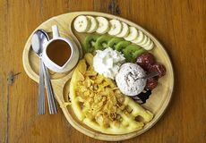 Sweet water pour on the waffle with ice cream and fruits including bananas, kiwi and strawberries in wooden plate on table royalty free stock photo