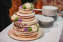 Sweet wedding cake with tiers decorated with flowers on white table. With plates Stock Image