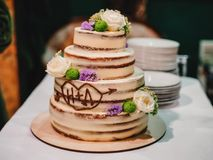 Sweet wedding cake with tiers decorated with flowers. Sweet wedding cake with tiers decorated with fresh flowers Royalty Free Stock Image