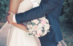Sweet wedding couple with gentle bouquet of peonies flowers, sensual groom hugging lovely bride. Outdoors Royalty Free Stock Photo