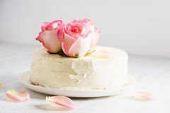 Sweet white buttercream cake with pink rose flowers on top Royalty Free Stock Photo