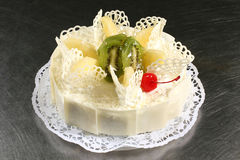 Sweet white cake with pineapple and kiwi on a gray background Royalty Free Stock Photos