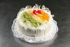 Sweet white cake with pineapple, kiwi and peach Stock Photos