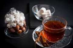 Sweet winter holidays background with various cookies and cup of hot spicy black tea on dark rustic table Royalty Free Stock Photo
