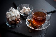 Sweet winter holidays background with various cookies and cup of hot spicy black tea on dark rustic table Stock Images