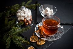 Sweet winter holidays background with various cookies and cup of hot spicy black tea on dark rustic table Royalty Free Stock Photos
