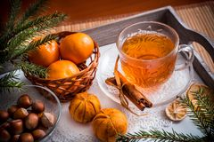 Sweet winter holidays background with various cookies and cup of hot spicy black tea on dark rustic table Royalty Free Stock Images