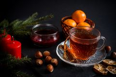 Sweet winter holidays background with various cookies and cup of hot spicy black tea on dark rustic table Stock Photography