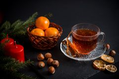 Sweet winter holidays background with various cookies and cup of hot spicy black tea on dark rustic table Stock Photo