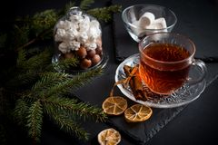 Sweet winter holidays background with various cookies and cup of hot spicy black tea on dark rustic table Royalty Free Stock Image