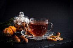 Sweet winter holidays background with various cookies and cup of hot spicy black tea on dark rustic table Stock Image