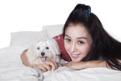 Sweet woman with maltese dog on bed. Attractive young woman lying on bed while embracing a maltese dog and smiling at the camera Royalty Free Stock Image