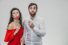 Sweet woman and man hold red fake lips on a stick. Have fun The wife is dressed in a red dress, a man in a white shirt. stock image