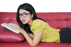 Sweet woman reading book on sofa Stock Photography