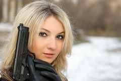 Sweet woman with a weapon Royalty Free Stock Photo