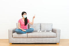 Sweet woman wearing medical mask sitting on sofa. Beautiful sweet woman wearing medical mask sitting on sofa couch in wooden floor and pointing to white Stock Photography