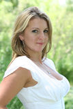Sweet woman in white blouse. A portrait of a sweet, pretty blonde woman in a white blouse stock image