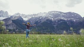 Sweet woman in a wreath is walking on alpine meadow, happily whirling with hands up. 4k stock footage
