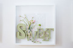 Sweet. Wood letters with rings. Green letters and flowers. Stock Image