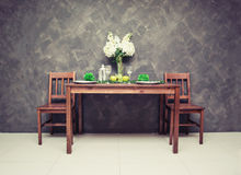 Sweet wooden dining table and chair with the wine glass and fruit on the table royalty free stock photo
