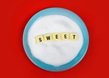 Sweet word block letters on bed of sugar in blue dish over red mat in sugar addiction Stock Photography