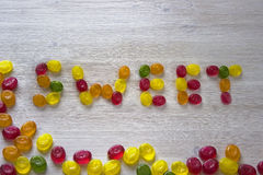 Sweet word made from candies. On white wooden background Royalty Free Stock Photos