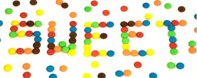 Sweet word written with colorful button shaped chocolates candy Royalty Free Stock Images
