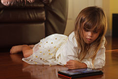 Sweet 4 year old girl in white, playing with iPad Royalty Free Stock Image