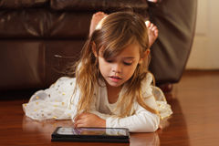 Sweet 4 year old girl in white, playing with iPad. Precious little girl with brown hair and wearing white skirt and top is lying on her stomach on a wood floor Royalty Free Stock Photography