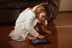 Sweet 4 year old girl in white, playing with iPad Royalty Free Stock Photography