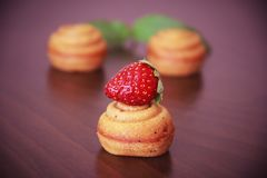 Sweet yellow biscuit cakes shells with strawberry decor royalty free stock images