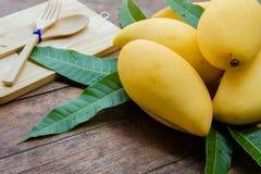 Sweet yellow mango fruit on summer on wood table.  Stock Photos
