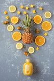 Sweet yellow smoothie with pineapple, citrus and yellow fruits on gray wooden table, top view.  Royalty Free Stock Photography