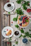 Sweet yoghurt cake with berries and biscuits served with coffee Stock Photography