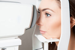 Sweet young adult brunette looking at eye test machine in ophtha Royalty Free Stock Photo