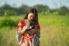 Sweet young Asian Chinese or Korean woman on her 20s checking picture in photo camera in beautiful nature landscape in holidays. And photographer hobby concept Stock Images