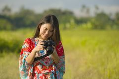 Sweet young Asian Chinese or Korean woman on her 20s checking picture in photo camera in beautiful nature landscape in holidays. Sweet young Asian Chinese or Royalty Free Stock Images